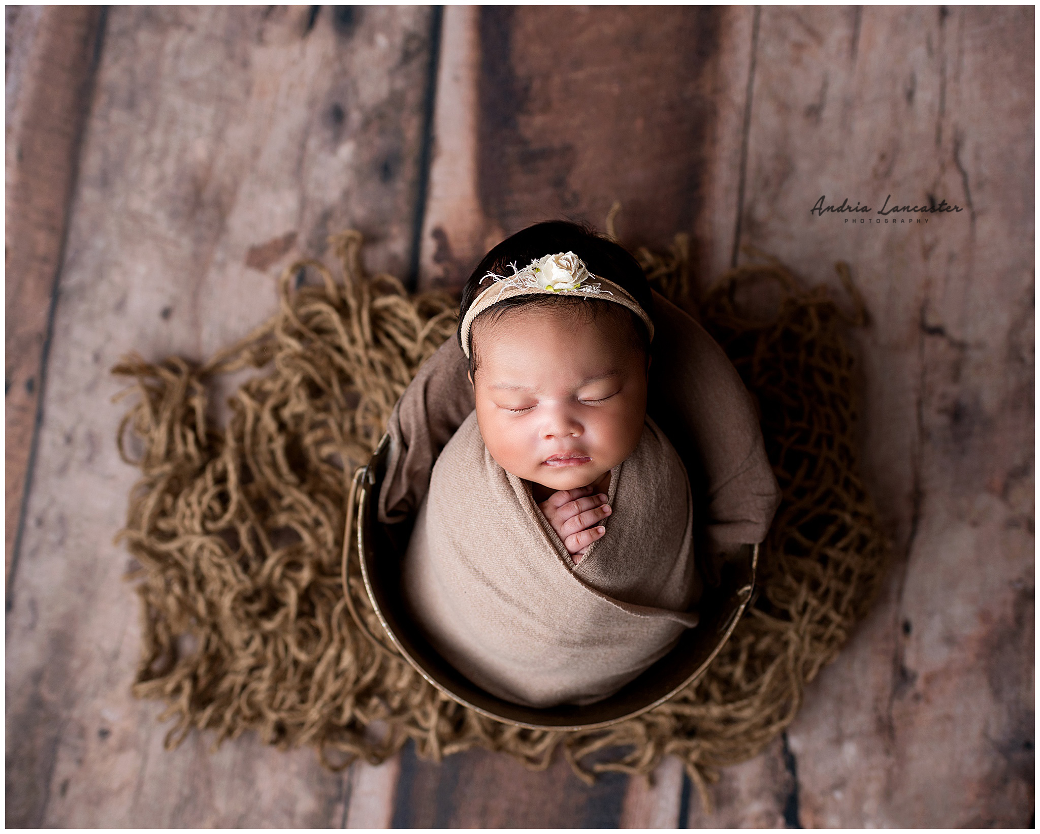 Newborn wrapped in bucket looking up