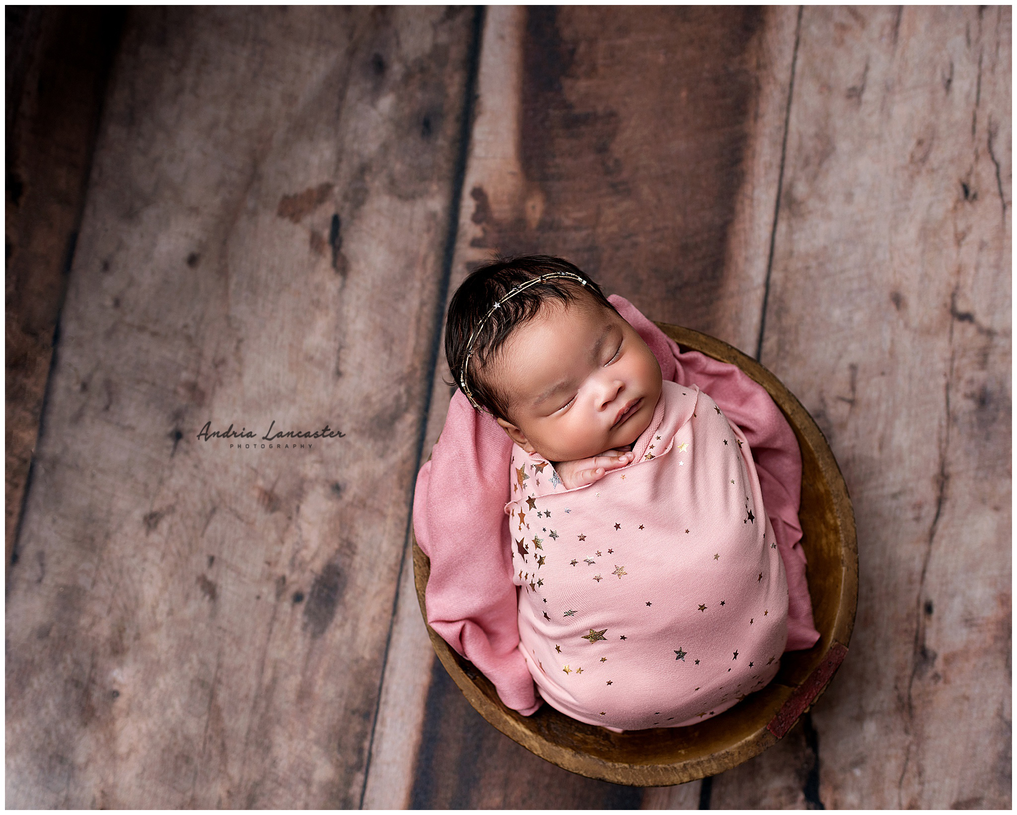 Newborn wrapped in pink with star headband in a bowl