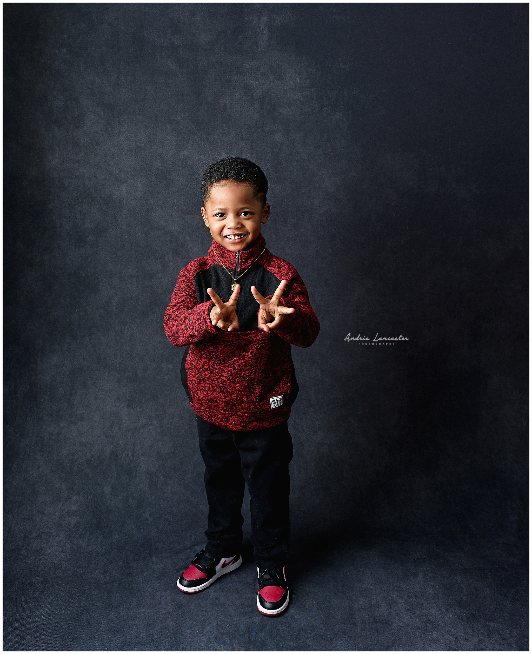 Boy holding up 3 fingers on each hand