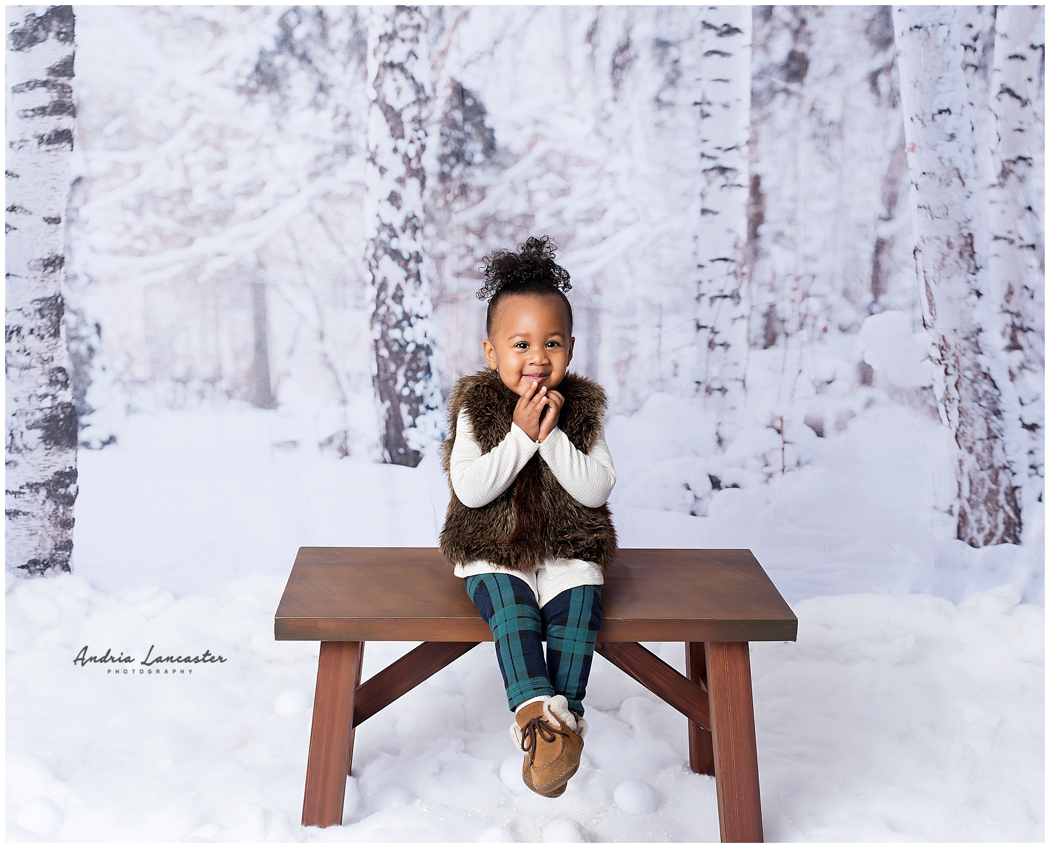 little girl sitting smiling with hands on face