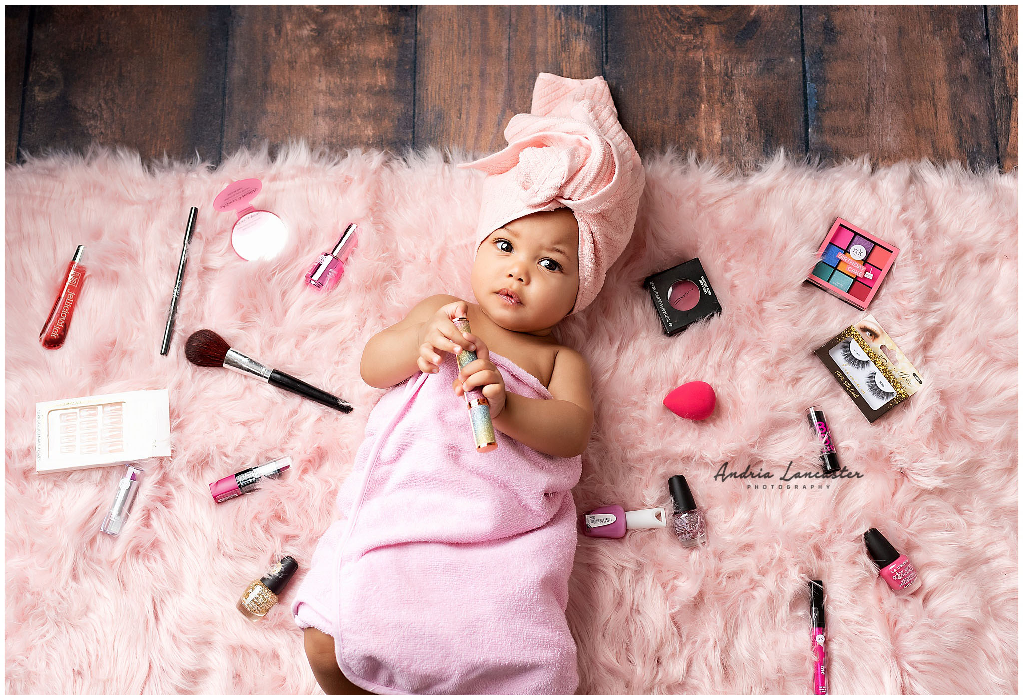 baby with towel on head laying on rug with makeup items