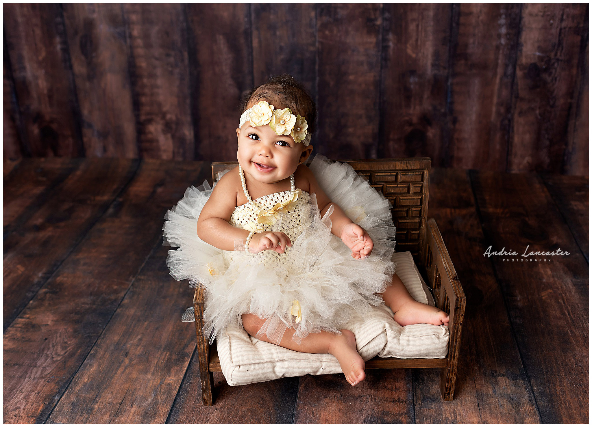 6 month old in studio sitting on bench smiling