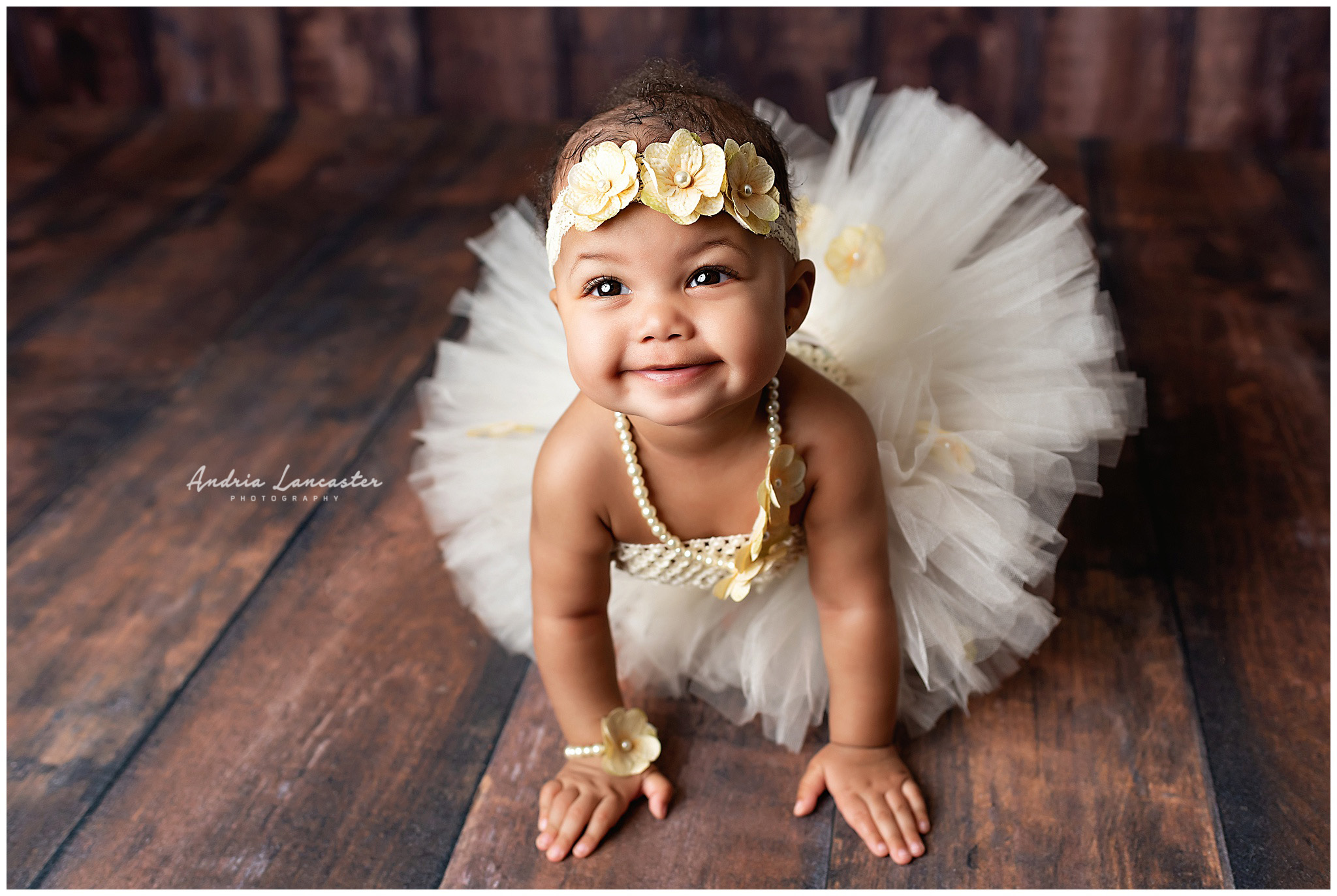 6 month old wearing tutu outfit with flowers looking up