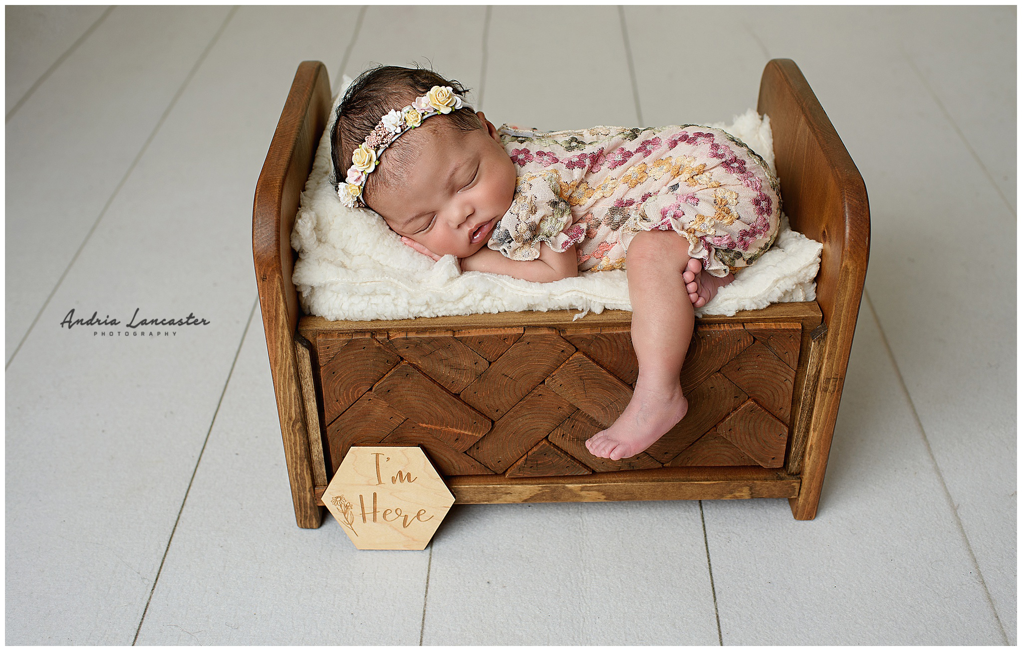 newborn in wooden bed prop with one leg of bed