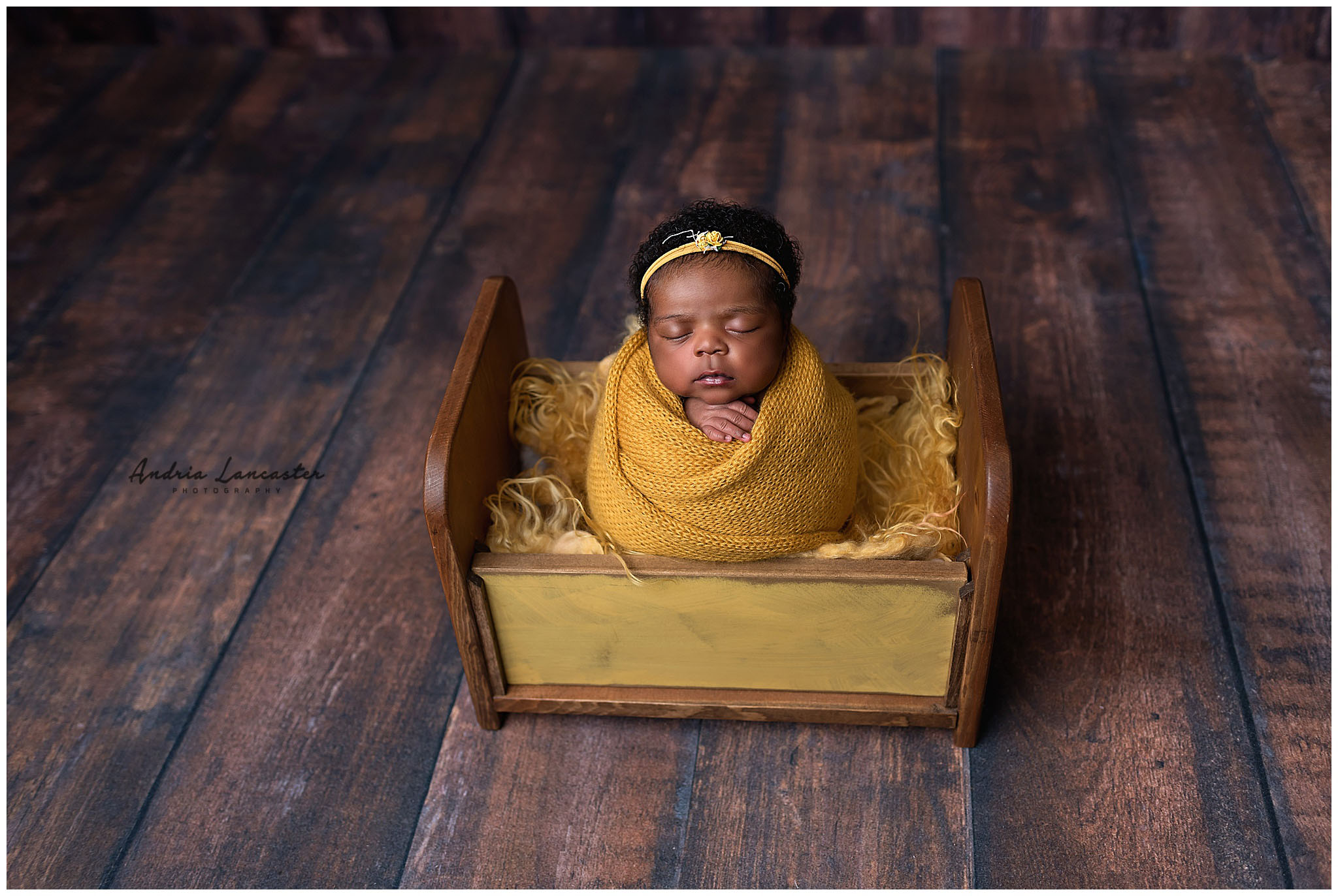 newborn wrapped in bed prop mustard colors