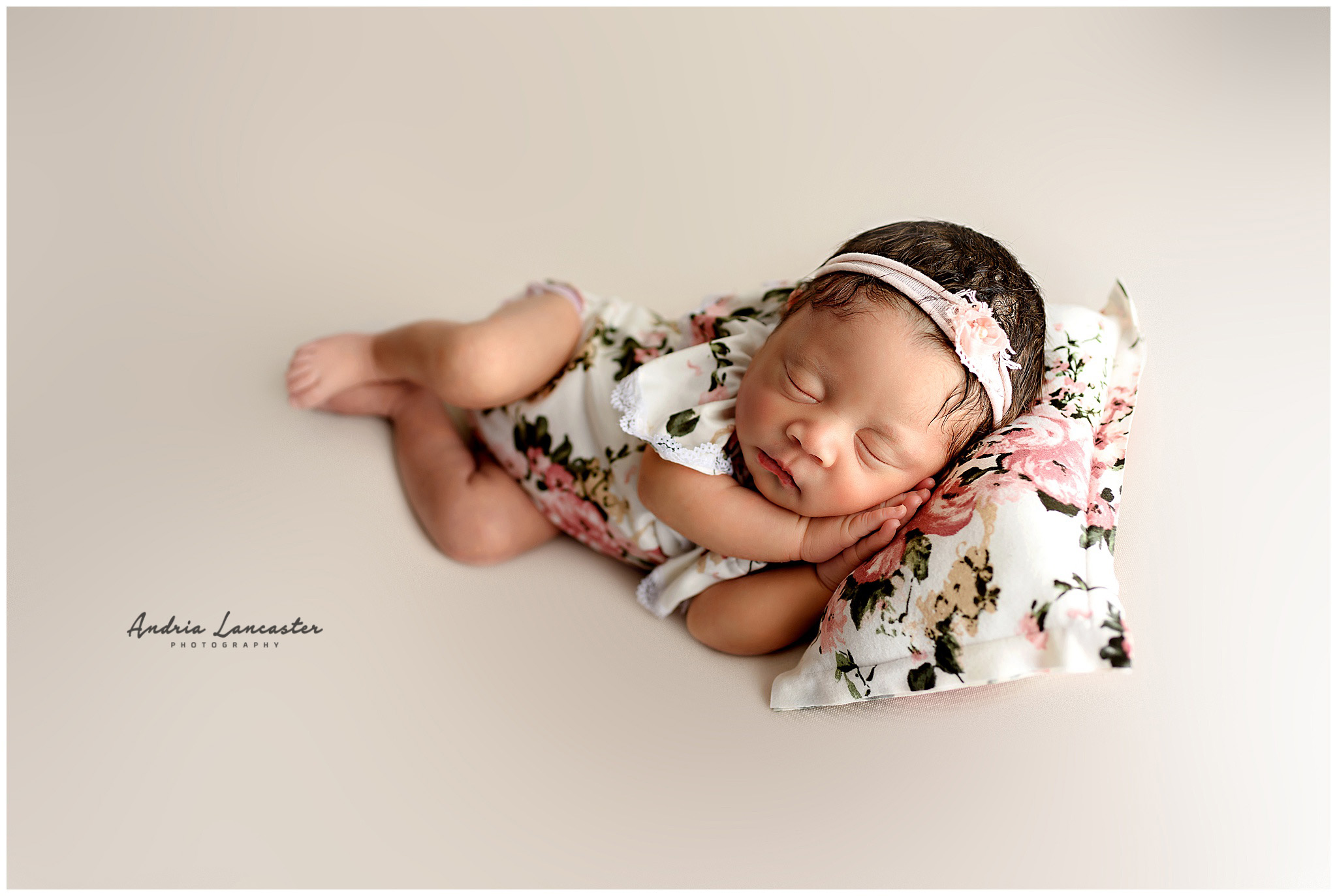 newborn in side laying pose on pillow pink floral