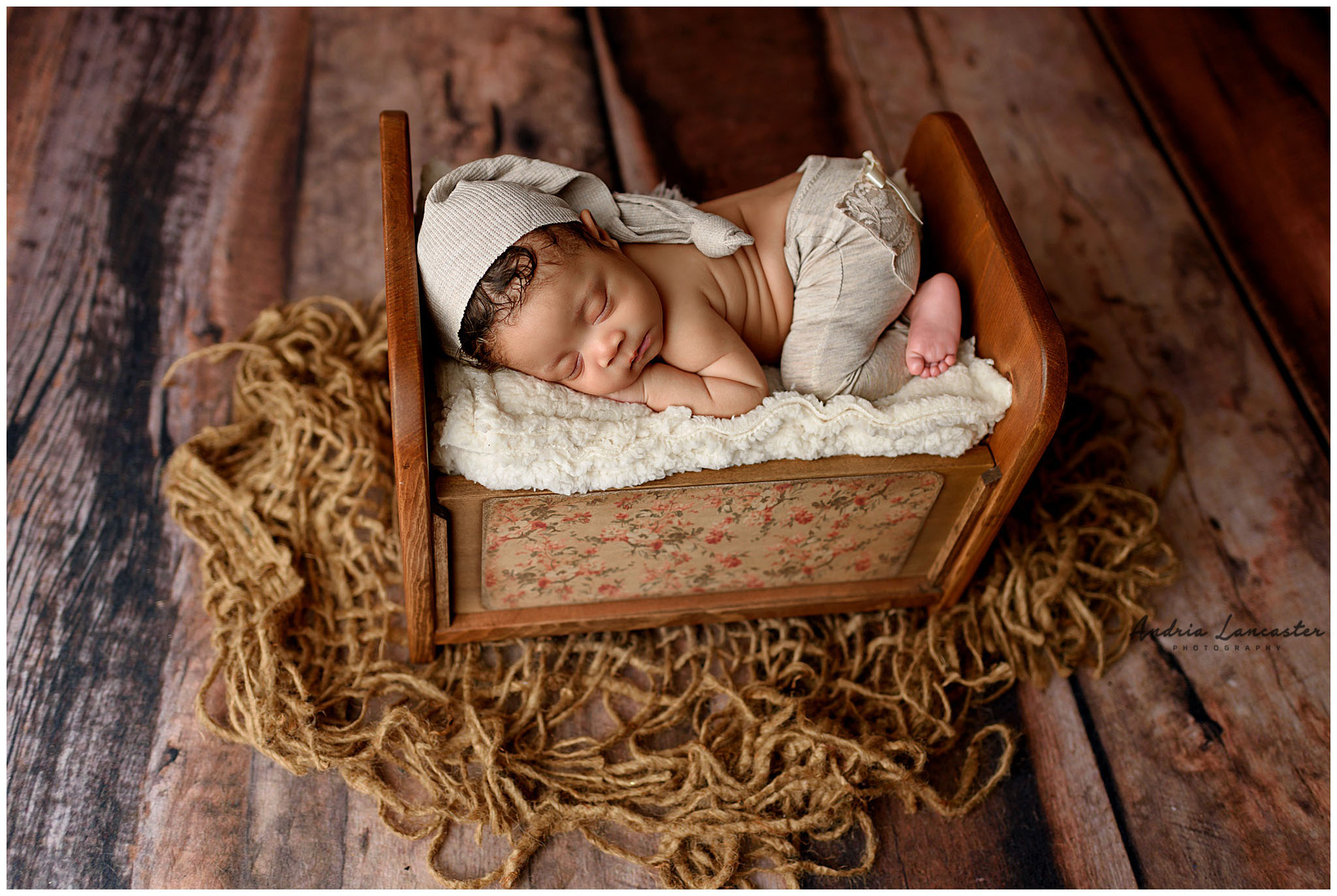newborn posed on bed wearing pants with bow and sleepy cap