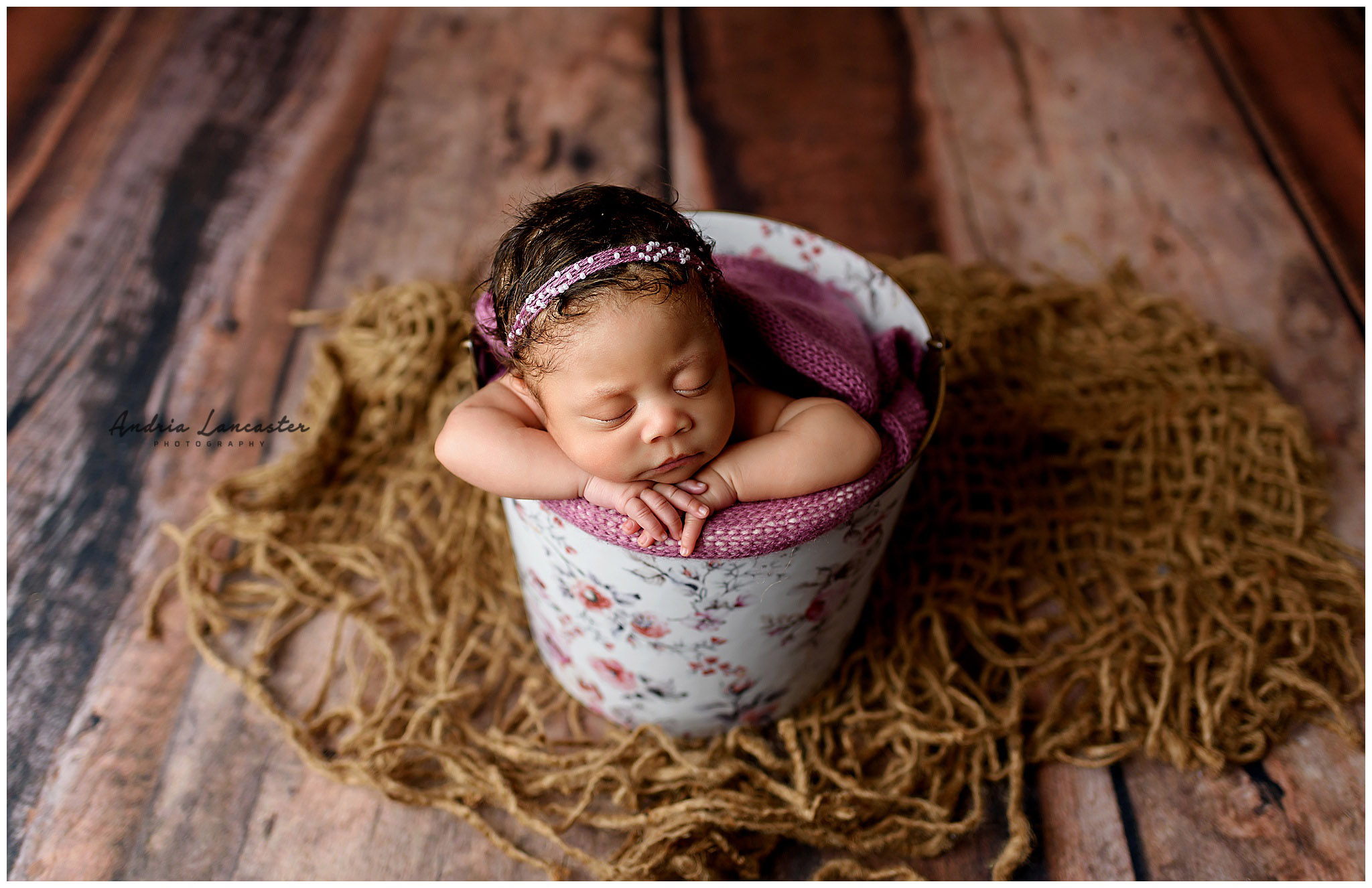 newborn in floral bucket and pink wrap