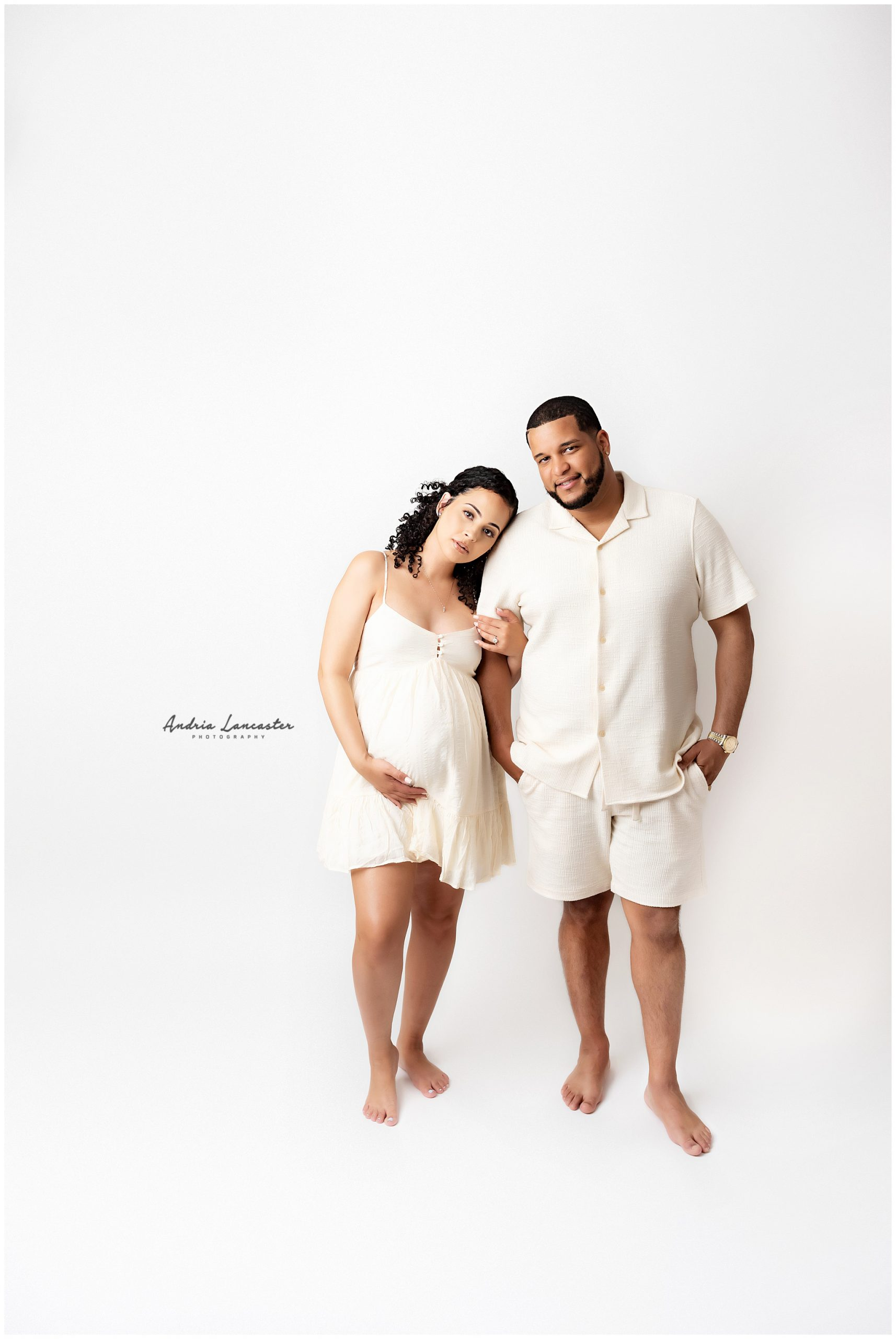 couple in studio maternity session off white outfits